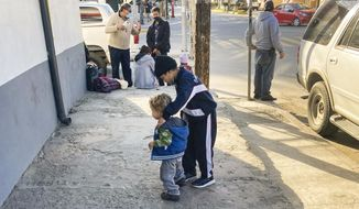 Honduran boys whose family wants to seek asylum in the U.S., play on the sidewalk in Tijuana, Mexico, Monday, Feb. 8, 2021. Thousands of people are waiting to claim asylum and more come each day, falsely believing they will be able to enter the U.S. now that former President Donald Trump is out of office. While President Joe Biden has taken some major steps in his first weeks in office to reverse Trump's hardline immigration policies, his administration hasn't lifted some of the most significant barriers to asylum-seekers.  (AP Photo/Elliot Spagat)
