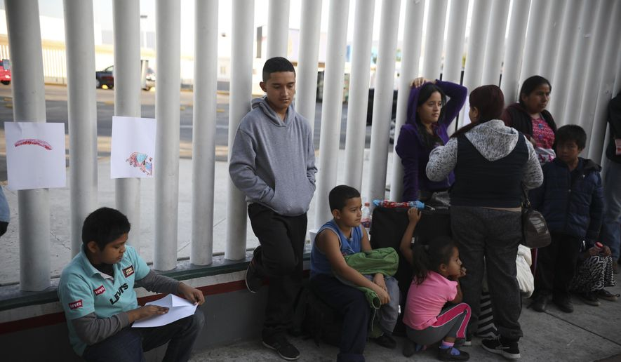 In this Sept. 13, 2019, file photo, Central American migrants wait to see if their number will be called to cross the border and apply for asylum in the United States, at the El Chaparral border crossing in Tijuana, Mexico. Thousands of people are waiting to claim asylum and more come each day, falsely believing they will be able to enter the U.S. now that former President Donald Trump is out of office. While President Joe Biden has taken some major steps in his first weeks in office to reverse Trump's hardline immigration policies, his administration hasn't lifted some of the most significant barriers to asylum-seekers. (AP Photo/Emilio Espejel, File)