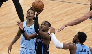 Sacramento Kings guard De'Aaron Fox, center, goes to the basket between Memphis Grizzlies' Ja Morant, left, and Xavier Tillman during the first half of an NBA basketball game in Sacramento, Calif., Sunday, Feb. 14, 2021. (AP Photo/Rich Pedroncelli)