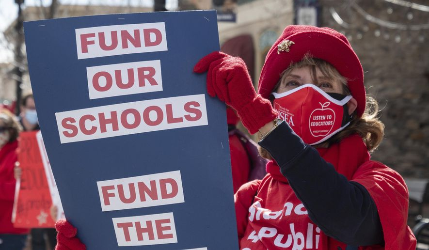 Nevada teachers and the Nevada State Education Association hold a rally demanding more funding outside of the state Legislature in Carson City, Nev., Monday, Feb. 15, 2021. As the state struggles to balance its budget amid the pandemic, teachers and their unions want lawmakers to find new revenue streams to fund education and are backing a proposal to raise taxes on the mining industry. (Bob Conrad/This Is Reno via AP, Pool) ** FILE **