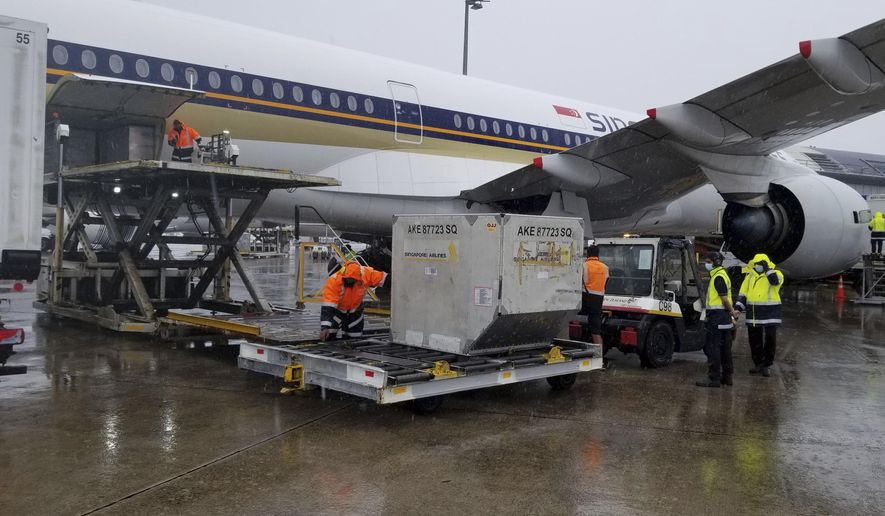 In this photo provided by New Zealand Ministry of Health, a shipment containing coronavirus vaccines is unloaded from a plane upon arrival in Auckland as New Zealand receives its first batch Monday, Feb. 15, 2021. Officials said the shipment of about 60,000 doses of the vaccine developed by Pfizer would initially be prioritized for border workers. (New Zealand Ministry of Health via AP)