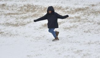 Kynlee Kelly, 8, plays in the snow near an apartment complex on William Boulevard. in Ridgeland, Miss., Monday, Feb. 15, 2021. According to the National Weather Service, a winter storm warning continues for all counties in Mississippi. (Eric Shelton/The Clarion-Ledger via AP)
