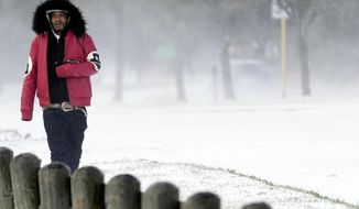 Igee Cummings walks through the snow Monday, Feb. 15, 2021, in Houston. A winter storm dropping snow and ice sent temperatures plunging across the southern Plains, prompting a power emergency in Texas a day after conditions canceled flights and impacted traffic across large swaths of the U.S. (AP Photo/David J. Phillip)