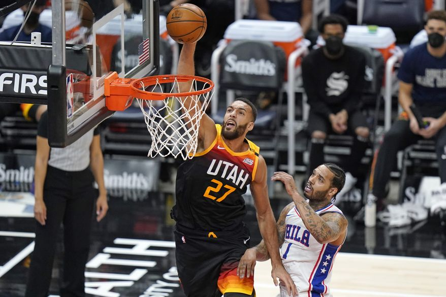 Utah Jazz center Rudy Gobert (27) dunks the ball against Philadelphia 76ers forward Mike Scott (1) in the first half during an NBA basketball game Monday, Feb. 15, 2021, in Salt Lake City. (AP Photo/Rick Bowmer)