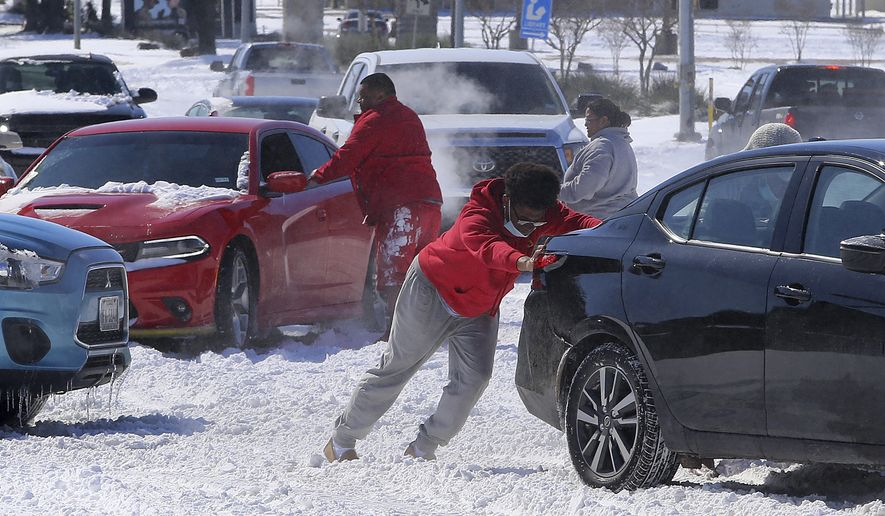 People push a car free after spinning out in the snow Monday, Feb. 15, 2021 in Waco, Texas. A winter storm that brought snow, ice and plunging temperatures across the southern Plains and caused a power emergency in Texas stretched its frigid fingers down to the Gulf Coast.  (Jerry Larson/Waco Tribune-Herald via AP)