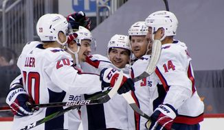 Washington Capitals' Conor Sheary, center, celebrates with teammates after scoring against the Pittsburgh Penguins during the second period of an NHL hockey game Tuesday, Feb. 16, 2021, in Pittsburgh. (AP Photo/Keith Srakocic)