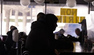 Patrons sit in restaurant without power caused by cold weather blackouts Tuesday, Feb. 16, 2021, in Richardson, Texas.  Temperatures dropped into the single digits as snow shut down air travel and grocery stores. (AP Photo/LM Otero)
