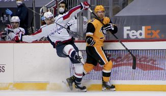 Pittsburgh Penguins' Mike Matheson (5) checks Washington Capitals' Garnet Hathaway (21) off the puck during the second period of an NHL hockey game Tuesday, Feb. 16, 2021, in Pittsburgh. (AP Photo/Keith Srakocic)