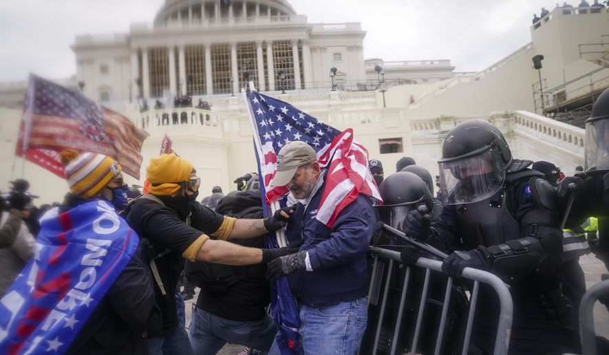 FILE - In this Jan. 6, 2021, file photo rioters try to break through a police barrier at the Capitol in Washington. People charged in the attack on the U.S. Capitol left behind a trove of videos and messages that have helped federal authorities build cases. In nearly half of the more than 200 federal cases stemming from the attack, authorities have cited evidence that an insurrectionist appeared to have been inspired by conspiracy theories or extremist ideologies, according to an Associated Press review of court records. (AP Photo/John Minchillo, File)