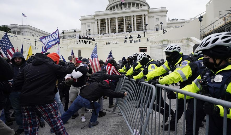 In this Jan. 6, 2021, file photo, rioters try to break through a police barrier at the U.S. Capitol in Washington. (AP Photo/Julio Cortez, File)  **FILE**