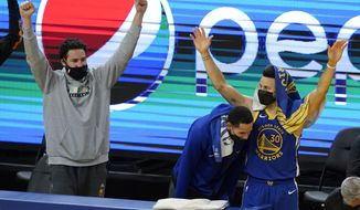 Injured Golden State Warriors guard Klay Thompson, from left, celebrates with Juan Toscano-Anderson and Stephen Curry during the second half of an NBA basketball game against the Cleveland Cavaliers in San Francisco, Monday, Feb. 15, 2021. (AP Photo/Jeff Chiu)