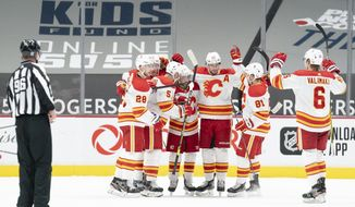 The Calgary Flames celebrate their game winning goal by left wing Johnny Gaudreau (13) during the third period of an NHL hockey game against the Vancouver Canucks, Monday, Feb. 15, 2021 in Vancouver, British Columbia. (Jonathan Hayward/The Canadian Press via AP)