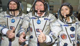 FILE - In this July 5, 2001 file photo, French astronaut Claudie Haignere, right, and her Russian crewmates Viktor Afanasyev, center, and Konstantin Kozeyev train inside the mock-up of a Soyuz TM spacecraft in Star City. The ESA, NASA's European equivalent, is highlighting diversity in the drive: The final frontier for such predominantly white and male agencies. This year the ESA is looking to recruit more women astronauts, as well as people with disabilities who always dreamed of going into space.(AP Photo/Mikhail Metzel, File)