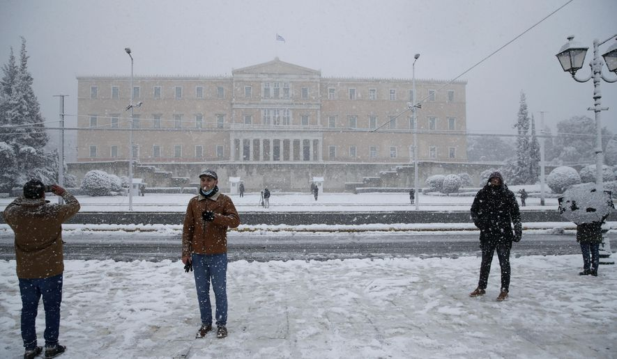 People take photographs as snow falls in front of the Greek parliament in Athens, Tuesday, Feb.16, 2021. A cold weather front has hit Greece, sending temperatures plunging from the low 20s Celsius (around 70 Fahrenheit) on Friday to well below freezing on Tuesday, and heavy snowfall in central Athens. (AP Photo/Thanassis Stavrakis)