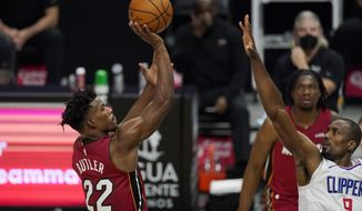 Miami Heat forward Jimmy Butler, left, shoots as Los Angeles Clippers center Serge Ibaka defends during the first half of an NBA basketball game Monday, Feb. 15, 2021, in Los Angeles. (AP Photo/Mark J. Terrill)