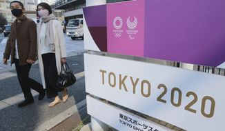 People walk by signage to promote the Olympic Games, in Tokyo, Tuesday, Feb. 16, 2021. The Olympics are scheduled to open on July 23 but recent polls show about 80% of the Japanese public want the Olympics canceled or postponed. (AP Photo/Koji Sasahara)