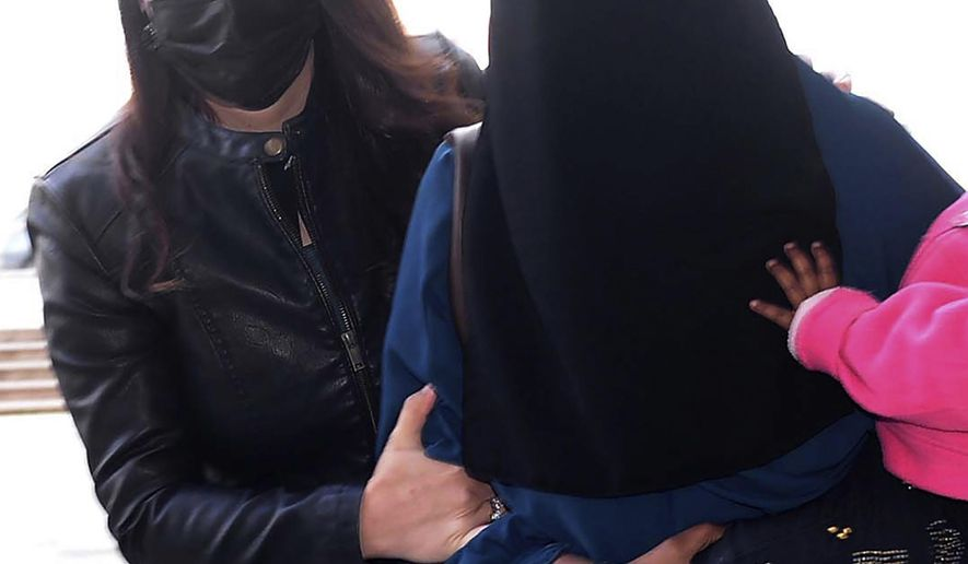 A woman, who was identified only by her initials S.A., one of three New Zealand nationals, is escorted by a Turkish police officer, left, to the local courthouse in Hatay, Turkey, Monday, Feb. 15, 2021.  According to a statement Monday by Turkey's Defense Ministry the 26-year old woman identified as S.A. is wanted on an Interpol notice for allegedly belonging to the extremist Islamic State group. (DHA via AP)