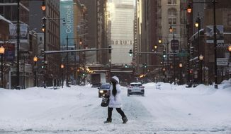 A woman crosses Wabash Avenue Tuesday, Feb. 16, 2021, after an overnight storm dumped up to 18.5 inches in the Chicago area. (AP Photo/Charles Rex Arbogast)