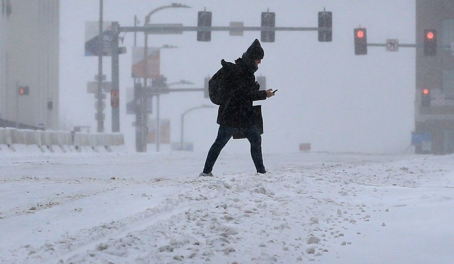 A pedestrian crosses Market Street during a snowstorm in downtown St. Louis on Monday, Feb. 15, 2021. The brutally cold weather is expected to continue through Saturday with more snow in the forecast for Wednesday and Thursday. (David Carson/St. Louis Post-Dispatch via AP)