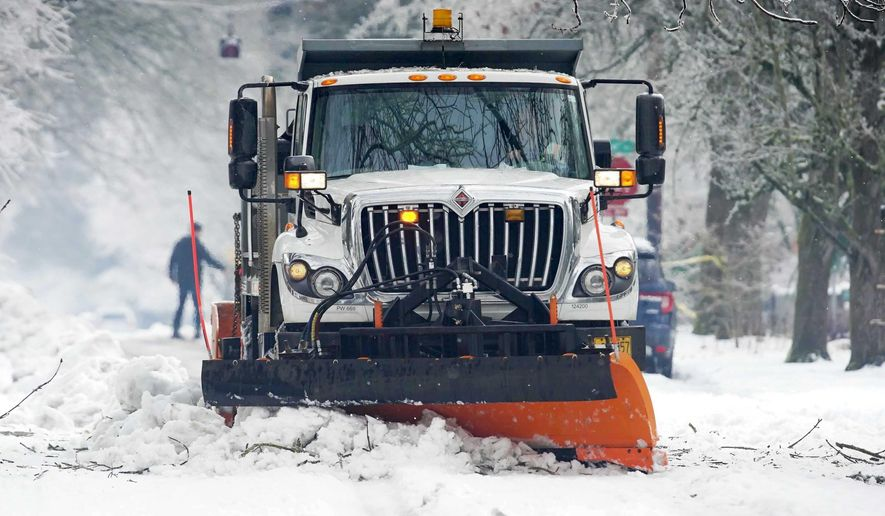 A snow plow clears snow off a street, Monday, Feb. 15, 2021, in Portland, Ore. (Beth Nakamura/The Oregonian via AP)