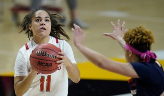 Maryland guard Katie Benzan, left, shoots against Illinois guard J-Naya Ephraim during the first half of an NCAA college basketball game, Wednesday, Feb. 17, 2021, in College Park, Md. (AP Photo/Julio Cortez)