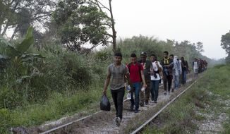 Migrants walk on train tracks on their journey from Central America to the U.S. border., in Palenque, Chiapas state, Mexico, Wednesday, Feb. 10, 2021. President Joe Biden's administration has taken steps toward rolling back some of the harshest policies of ex-President Donald Trump, but a policy remains allowing U.S. border officials to immediately send back almost anyone due to the new coronavirus pandemic. (AP Photo/Isabel Mateos)