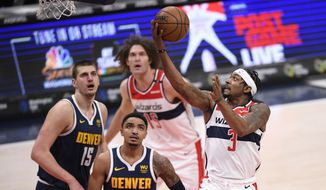 Washington Wizards guard Bradley Beal (3) goes to the basket against Denver Nuggets center Nikola Jokic (15) and guard Gary Harris (14) during the first half of an NBA basketball game, Wednesday, Feb. 17, 2021, in Washington. (AP Photo/Nick Wass)