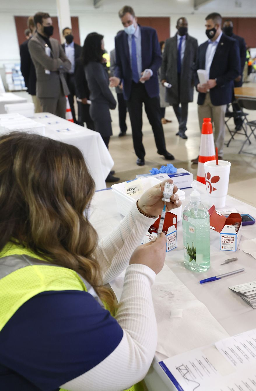Ashleigh Trobaugh, an RN at Godwin High School, draws the second Moderna vaccine that is being given to people at the Richmond Raceway Complex in Richmond, Va., Wednesday, Feb. 17, 2021. Sen. Mark Warner was touring the operation. (Alexa Welch Edlund/Richmond Times-Dispatch via AP)