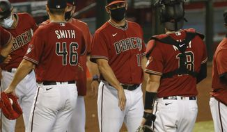 FILE - Arizona Diamondbacks baseball team manager Torey Lovullo, center, greets his players after their win over the Colorado Rockies in Phoenix, in this Sunday, Sept. 27, 2020, file photo. The 55-year-old Lovullo enters his fifth year with the Diamondbacks  — and the final year of his current contract — under a substantial amount of scrutiny. Lovullo shrugged off any notion that he's feeling added pressure on Wednesday, Feb. 17, 2021, when the team's pitchers and catchers went through their first workouts in Scottsdale, Arizona. (AP Photo/Darryl Webb, File)
