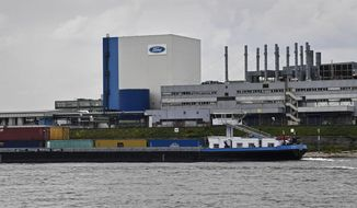 FILE - In this May 4, 2020 file photo, a container ship passes the Ford car plant in Cologne, Germany, as the US car maker restarts the production after the coronavirus lockdown. Ford says it will spend $1 billion to modernize its Cologne, Germany, manufacturing center, converting it into a European electric vehicle factory. (AP Photo/Martin Meissner)