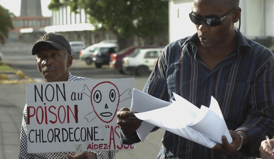 """In this Nov. 18, 2007 photo, lawyer Harry Durimel, right, stands next to an activist with a sign that reads in French """"No to Chlordecone poison,"""" as they protest during the arrival of the French government's Health Minister Roselyne Bachelot in Raizet Abymes, Guadeloupe. Durimel is among the attorneys representing agricultural workers in Guadeloupe and Martinique who have long been fighting for compensation for the use of a banned pesticide, chlordecone. (AP Photo/Dominique Chomereau-Lamotte)"""