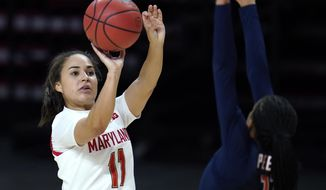 Maryland guard Katie Benzan, left, shoots against Illinois guard Jada Peebles during the second half of an NCAA college basketball game, Wednesday, Feb. 17, 2021, in College Park, Md. (AP Photo/Julio Cortez)