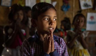 """Imradul Ali, 10, prays with others in a classroom in a school near a landfill on the outskirts of Gauhati, India, Friday, Feb. 5, 2021. Once school is done for the day, Ali, rushes home to change out of his uniform so that he can start his job as a scavenger in India's remote northeast. Coming from a family of scavengers or """"rag pickers,"""" Ali started doing it over a year ago to help his family make more money. Ali says he doesn't want to spend his life doing this, but he doesn't know what the future holds. (AP Photo/Anupam Nath)"""