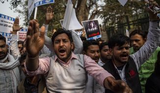 """Members of National Students Union of India (NSUI), the student body of the Congress party, shout slogans against the  government while condemning the arrest of Indian climate activist Disha Ravi, in New Delhi, India, Wednesday, Feb. 17, 2021. Ravi, 22, was arrested in Bengaluru on Saturday for circulating a document on social media supporting months of massive protests by farmers. Police said at a news conference on Monday that the document spread misinformation about the farmer protests on the outskirts of New Delhi and """"tarnished the image of India."""" (AP Photo/Altaf Qadri)"""