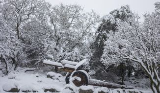 An old mobile artillery piece form Mideast wars sits covered with snow in a memorial site near the Quneitra border crossing between Syria and the Israeli-controlled Golan Heights Wednesday, Feb. 17, 2021. (AP Photo/Ariel Schalit)