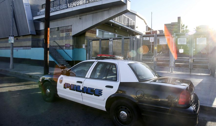 FILE - In this Dec. 15, 2015, file photo, a police car is parked outside of Miguel Contreras Learning Complex in Los Angeles. The board overseeing the Los Angeles Unified School District has cut $25 million from the budget for school police and will use the money to help fund an achievement plan for Black students. The plan was approved by the school board on Tuesday, Feb. 16, 2021. (AP Photo/Ringo H.W. Chiu, File)