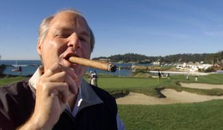 In this Feb. 3, 2001, file photo, Rush Limbaugh puffs on his Ashton VSG cigar while waiting to tee off from the fifth tee of the Pebble Beach Golf Links during third round play of the AT&T Pebble Beach National Pro-Am in Pebble Beach, Calif. Limbaugh, the talk radio host who became the voice of American conservatism, has died. His death Wednesday, Feb. 17, 2021, at the age of 70 was announced on his website. (AP Photo/Eric Risberg, File)