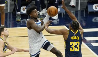 Minnesota Timberwolves' Anthony Edwards drives as Indiana Pacers' Myles Turner (33) defends during the first half of an NBA basketball game Wednesday, Feb. 17, 2021, in Minneapolis. (AP Photo/Jim Mone)
