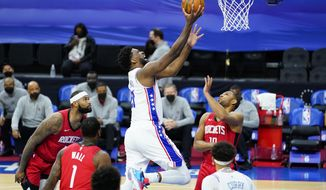 Philadelphia 76ers' Joel Embiid, center, goes up for a shot against Houston Rockets' Eric Gordon, right, during the second half of an NBA basketball game, Wednesday, Feb. 17, 2021, in Philadelphia. (AP Photo/Matt Slocum)