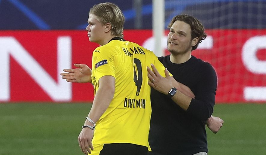 Dortmund's Erling Haaland, left is congratulated by Dortmund's head coach Edin Terzic at the end of the Champions League, round of 16, first leg soccer match between Sevilla and Borussia Dortmund at the Ramon Sanchez Pizjuan stadium in Seville, Spain, Wednesday, Feb. 17, 2021. (AP Photo/Angel Fernandez)