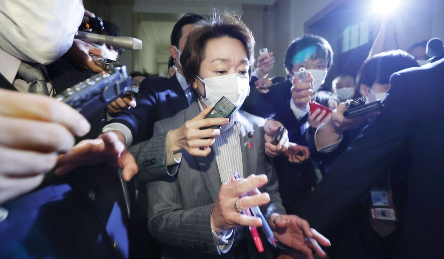 """Japan's Olympics Minister Seiko Hashimoto, center, is surrounded by reporters at the Lower House in Tokyo, Wednesday, Feb. 17, 2021. Japan's Kyodo news agency, citing a source """"familiar with the matter,"""" said a selection committee will ask Hashimoto to become the new president of the Tokyo Olympic organizing committee. Hashimoto, who could be named this week, would replace Yoshiro Mori who was forced to resign last week after he made demeaning comments about women — basically saying they talk too much.(Meika Fujio/Kyodo News via AP)"""