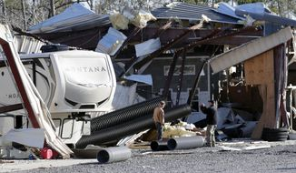 Owner Richard Dobkin, right, photographs the damage at Ocean Ridge Storage Solutions in Brunswick County, N.C. near the town of Sunset Beach, Wednesday, Feb. 17, 2021.  Officials say a ferocious tornado struck shortly before midnight Monday just inland from the barrier island of Ocean Isle Beach.(AP Photo/Chris Seward)