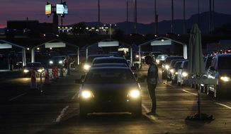 FILE - In this Jan. 12, 2021, file photo, vehicles line up so people can get their COVID-19 vaccination cards after being vaccinated in a pre-registered drive-thru in the parking lot of the State Farm Stadium in Glendale, Ariz. Arizona reported COVID-19 pandemic totals of over 800,000 confirmed cases and more than 15,000 deaths, passing the two grim milestones Wednesday, Feb. 17, 2021, after nearly 13 months since the coronavirus outbreak was first reported in the state. (AP Photo/Ross D. Franklin, File)
