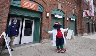 Boston Red Sox mascot, Wally the Green Monster, gestures while dressed in a medical white coat outside Fenway Park, Monday Feb. 1, 2021, in Boston. Fenway Park is one of several large COVID-19 vaccination sites in the Boston area. (AP Photo/Elise Amendola)