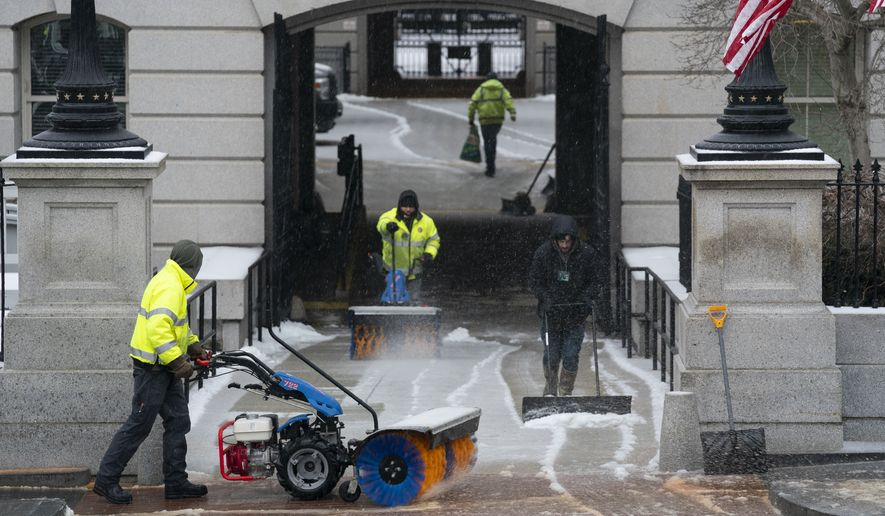 Workers from the National Park Service clear snow and ice outside the Eisenhower Executive Office building on the White House campus, Thursday, Feb. 18, 2021, in Washington. (AP Photo/Evan Vucci)