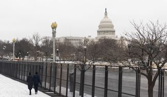The U.S. Capitol is seen behind the metal security fencing around the U.S. Capitol, Thursday, Feb. 18, 2021. U.S. Capitol Police officials told congressional leaders the razor-wire topped fencing around the Capitol should remain in place for several more months as law enforcement continues to track threats against lawmakers, a person familiar with the matter told The Associated Press on Thursday. (AP Photo/Manuel Balce Ceneta)