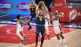 Washington Wizards guard Bradley Beal (3) reaches for the ball against Denver Nuggets center Nikola Jokic (15) during the first half of an NBA basketball game, Wednesday, Feb. 17, 2021, in Washington. Also seen is Washington Wizards forward Rui Hachimura (8), of Japan. (AP Photo/Nick Wass)