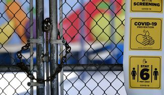 In this July 13, 2020, file photo, a gate is locked at the closed Ranchito Elementary School in the San Fernando Valley section of Los Angeles. After weeks of tense negotiations, California legislators agreed Thursday, Feb. 18, 2021, on a $6.5 billion proposal aimed at getting students back in classrooms this spring following months of closures because of the pandemic. (AP Photo/Richard Vogel, File)