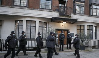Police officers stand outside King Edward VII's hospital in London, Thursday, Feb. 18, 2021. Buckingham Palace says 99-year-old Prince Philip has been admitted to a London hospital after feeling unwell. The palace said the husband of Queen Elizabeth II was admitted to the private King Edward VII Hospital on Tuesday evening. (AP Photo/Frank Augstein)