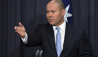 Australia's Treasurer Josh Frydenberg speaks at a press conference at Parliament House in Canberra, Thursday, Feb. 18, 2021. Frydenberg amended draft legislation after weekend talks with Facebook CEO Mark Zuckerberg and Sundar Pichai, chief executive of Alphabet Inc. and its subsidiary Google, to make it clear the platforms would not be charged per news snippet or link. (Mick Tsikas/AAP Image via AP)
